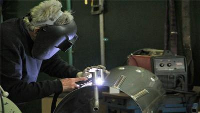 A welder at Eureka's Future factory in Melbourne works on a solar-powered water heater [Jarni Blakkarly/Al Jazeera]